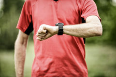 Runner looking at sport or smart watch checking pulse or gps Stock Photo