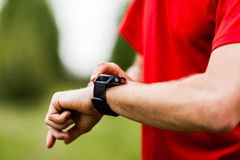Runner looking at sports watch Royalty Free Stock Photography