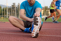 Runner making stretching. On the track Stock Image