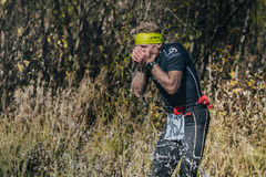 Runner man drinks water from a mountain stream Stock Images