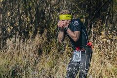 Runner man drinks water from a mountain stream. Beloretsk, Russia - September 26, 2015: runner man drinks water from a mountain stream during marathon mountain stock images