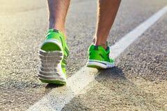 Runner man feet running on road closeup on shoe. stock images