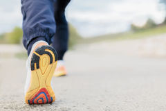 Runner Man Feet Running on Road closeup on shoe. Rear view Royalty Free Stock Photo