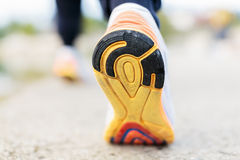 Runner Man Feet Running on Road closeup on shoe. Shot from rear view Royalty Free Stock Photos
