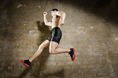Runner man jumping with dirty wall background Royalty Free Stock Photo