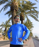 Runner man posing at beach palm trees boulevard with sunglasses in morning jog training session Royalty Free Stock Photos