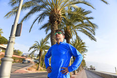 Runner man posing at beach palm trees boulevard with sunglasses in morning jog training session Royalty Free Stock Photo