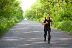 Runner man running on road training sprint. Sporting male run working out outside Stock Image