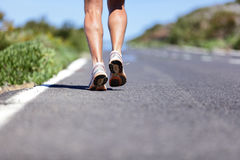 Runner man with running shoes on road to success. Road to success. Runner with determination running long distance endurance run on marathon race road. Closeup stock images
