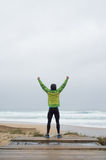 Runner man on the shore of the beach with hands up Royalty Free Stock Photography