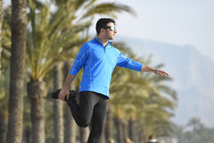 Runner man  stretching at beach palm trees boulevard with sunglasses in morning jog training session Royalty Free Stock Photography