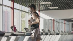 Runner man training on treadmill machine at workout in fitness center. Fitness man training cardio exercise on running machine in gym. Handsome runner looking stock video footage