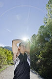 Runner man warming arms into the trees. Runner man warming arms and legs with sun light flare, warm up and stretching Royalty Free Stock Photos