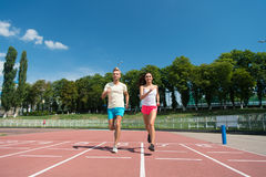 Runner man and woman running on arena track. Runner men and women sunny outdoor on blue sky running on arena track royalty free stock photography
