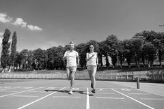 Runner man and woman running on arena track. Runner man and woman sunny outdoor on blue sky running on arena track royalty free stock photo