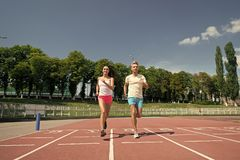 Runner man and woman running on arena track. Runner men and women sunny outdoor on blue sky running on arena track stock images