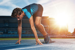 Runner on the mark at starting line. Young male runner taking ready to start position against bright sunlight. Sprinter on starting block of a racetrack in Royalty Free Stock Photos