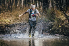 Runner middle-aged man crossing a mountain river. Beloretsk, Russia - September 26, 2015: runner middle-aged man crossing a mountain river during marathon royalty free stock image