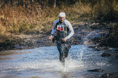 Runner middle-aged man crossing river, and around him water splashes. Beloretsk, Russia - September 26, 2015: runner middle-aged man crossing river, and around royalty free stock photo