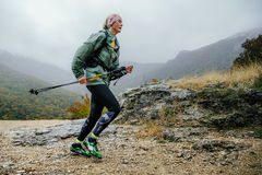 Runner middle-aged woman running in rain on a mountain trail with walking poles. Yalta, Russia - October 8, 2016: runner middle-aged woman running in rain on a Royalty Free Stock Photography