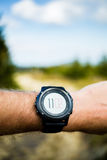Runner on mountain trail looking at stopwatch, activity tracker Royalty Free Stock Image
