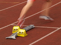 Runner Off the Starting Block. An athlete starts off the starting block at a track and field meeting Royalty Free Stock Images
