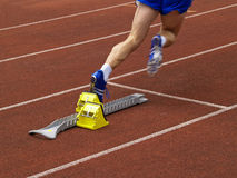 Runner Off the Starting Block. An athlete starts off the starting block at a track and field meeting Royalty Free Stock Photo