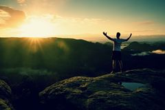 Runner on the peak. Man in his target gesture triumph with hands in the air. Crazy man in black pants and white cotton t-shirt, Royalty Free Stock Image