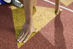 Runner Positioned On Starting Block. Cropped image of male athlete in starting block at racetrack Stock Images