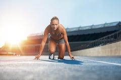 Runner practicing in athletics stadium Stock Photos
