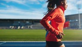 Runner practicing in athletics stadium Stock Photo