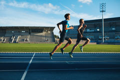 Runner practicing in athletics stadium. Shot of young male athlete launching off the start line in a race. Runner running on racetrack in athletics stadium royalty free stock photo