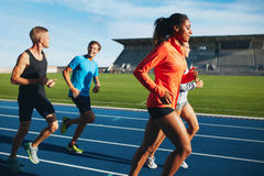 Runner practicing in athletics stadium. Shot of young male athlete launching off the start line in a race. Runner running on racetrack in athletics stadium Stock Photos