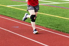 Running with a knee brace on. A runner is practicing on a red track while wearing a large black knee brace stock image