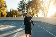 Runner practicing run on athletics running track. Sprinter training for marathon outdoor at sunset. Young man evening jog Royalty Free Stock Photo