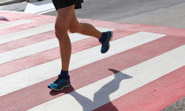 Runner during the race on the Pedestrian crossing Stock Photos