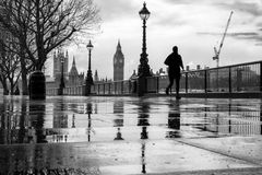 Runner in the rain. Silhouetted man running in the rain on London's Southbank, with Big Ben in background Stock Images