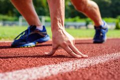 Runner ready to go close up. Ready steady go concept. At the beginning of great sport career. Hand touch track path. Close up. Hand of sportsman on running royalty free stock photography