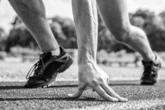 Runner ready to go close up. Ready steady go concept. At beginning of great sport career. Hand touch track path close up. Hand of sportsman on running track stock photo