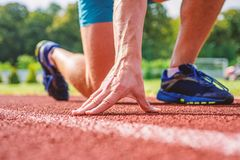 Runner ready to go close up. Ready steady go concept. At beginning of great sport career. Starting point. Hand touch. Track path close up. Hand of sportsman on stock photography