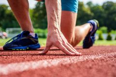 Runner ready to go close up. Ready steady go concept. At beginning of great sport career. Starting point. Hand touch. Track path close up. Hand of sportsman on stock image