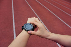 Runner ready to run set and looking at sports smart watch Stock Photography