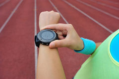 Runner ready to run set and looking at sports smart watch Stock Photos