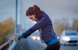 Runner rest during city workout. Athletic woman resting after jogging and leaning on a parapet of the bridge. Beautiful young woman relaxing after a jog in the Royalty Free Stock Photos