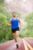 Runner - running athlete man. Male sprinting during outdoors training for marathon run. Athletic fit young sport fitness model in his twenties in full body Stock Image