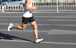 Runner running on city road. Marathon runner running on city road Stock Photos