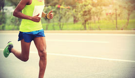 Runner running on city road. Marathon runner running on city road Royalty Free Stock Photography