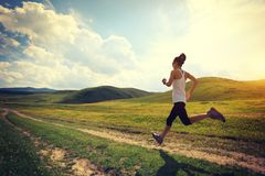 Runner running on grassland trail stock photos
