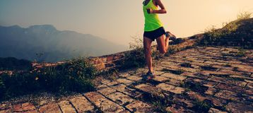 Runner running at great wall on the top of mountain. Fitness woman trail runner running at great wall on the top of mountain royalty free stock images