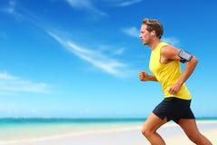 Runner running listening smartphone music on beach stock photos